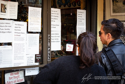 A couple looks over the many posting on Lotta's Bakery.