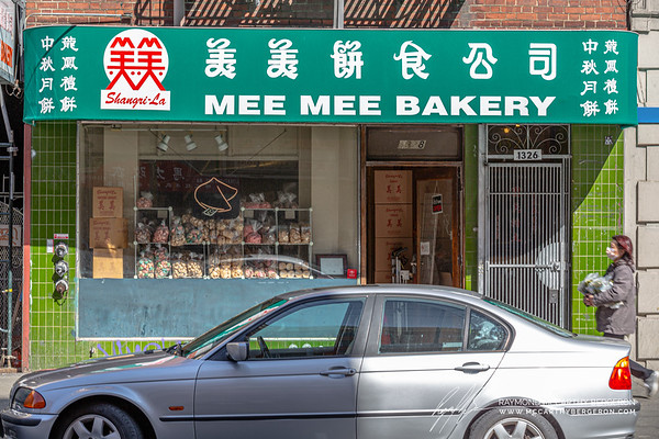 Woman carries a bag of goods past Mee Mee's open bakery.