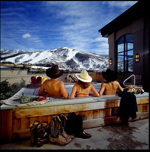 Steamboat Springs,  Adding people to hospitality shots which show the propertie's amenities can be difficult and nothing can be more deadly that tradition shots of a couple gazing into each others eyes.  This photo captures you attention, shows the facility, slopes, and hot tub, and is rich in detail. Three friends relaxing. Cowboy motif, and nice boots!