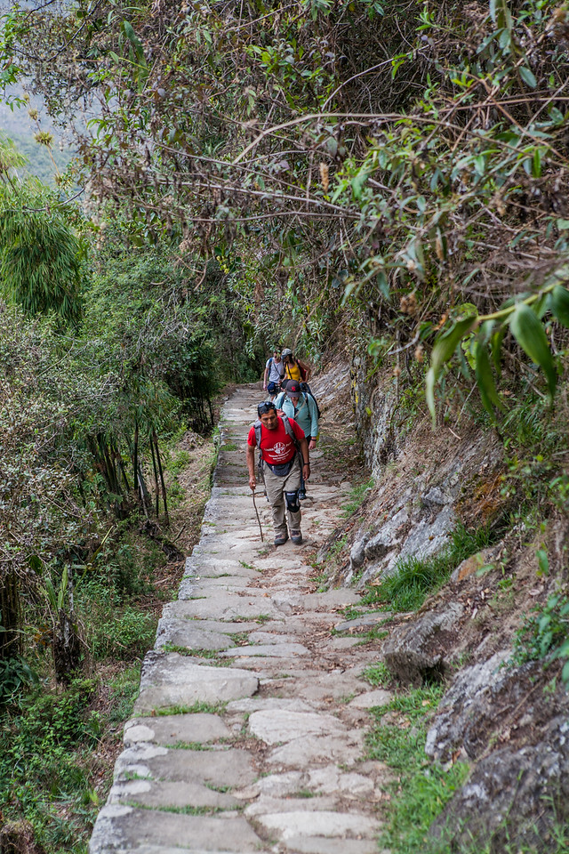 A group of trekkers completing their Inca trail, entering the Machu Picchu site through the Sun Gate