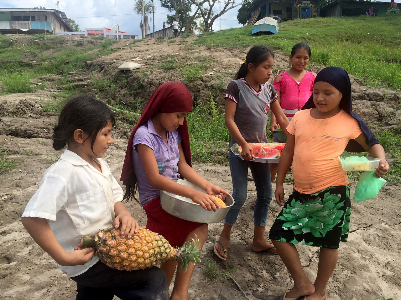 Little girls selling fruits on the boat from Iquitos to the border town of Peru in the Amazon rainforest