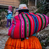 Cholitas carrying their wares up to their houses from the port at Yumani on Isla del Sol, an island on Lake Titicaca in Bolivia