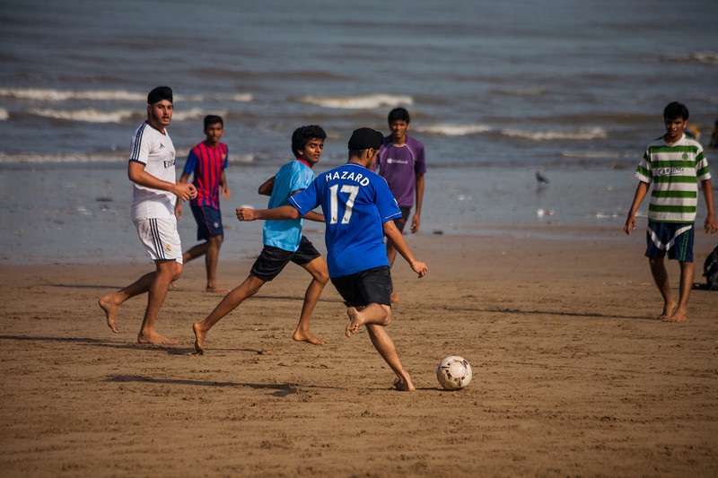Young boys playing football on the Juhu beach in Mumbai on a Sunday morning
