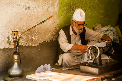 An old man, a tailor stitches clothes in his old shop in the Anantnag market of Kashmir with his hookah next to him.