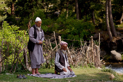 Two Muslim men perform their prayers, Namaz, in the Daksum Wildlife Sanctuary in Kashmir