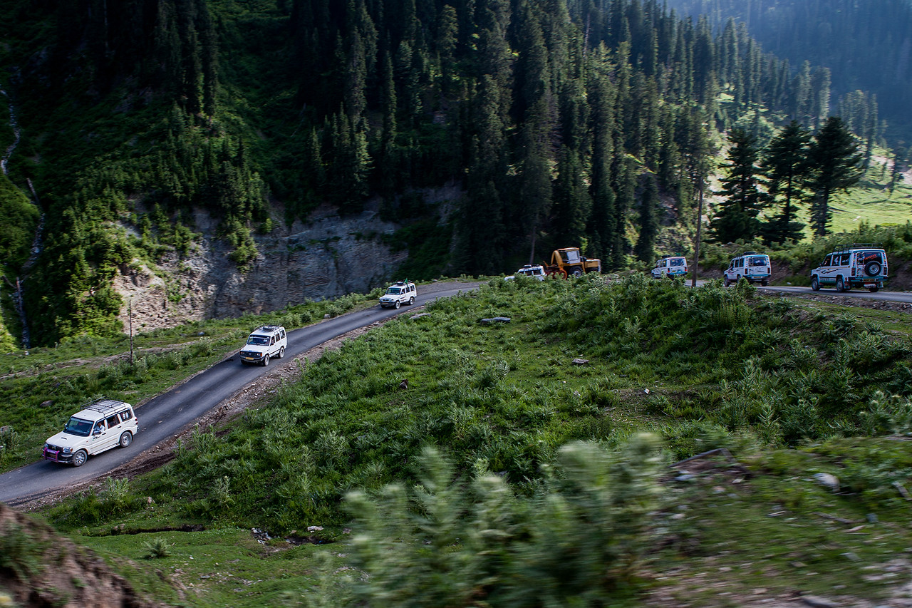 A convoy of seven jeeps on a road through the mountains covered with coniferous trees on the other