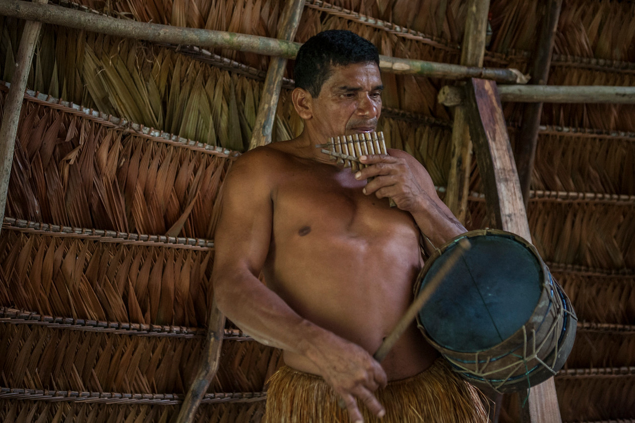 A Yagua man playing pan flute and drums for tourists, Peru