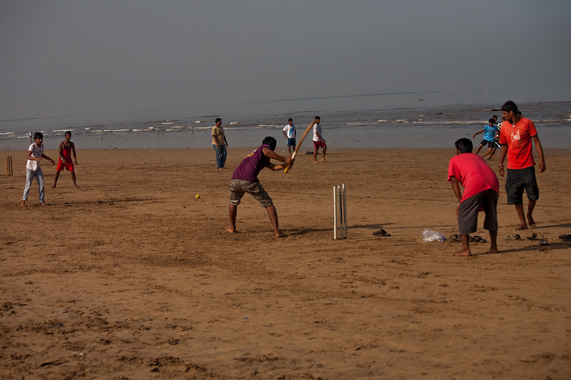 Young boys playing cricket on the Juhu beach in Mumbai on a Sunday morning
