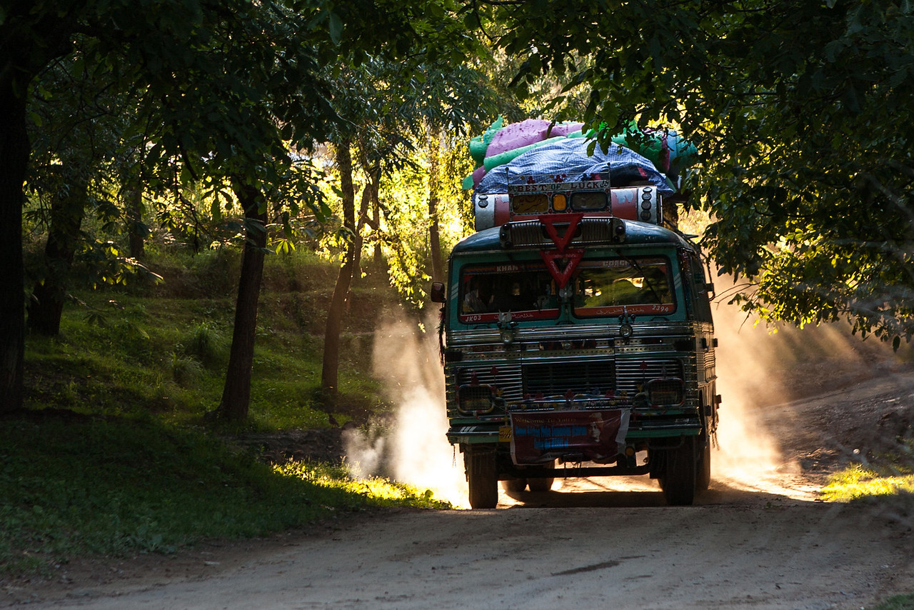Bus crosses the evening rays at sunset at Nagdandi near Achabal in Kashmir, India