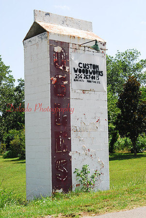A giant milk carton near Weogufka, Alabama. Once a sign for a local dairy, this 18 foot concrete and brick milk carton advertises for an auto body shop.
