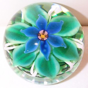 """DCP04137PE-Flower D4 Type....Strathearn Experimental Blue Flower magnum but with six petals & six variegated green leaves set up on a terrific emerald green & white crisscross lattice ribbon cushion 3.45"""" x 2.55"""" & 28 ozs. Center cane is a 1979 to 1980 creation and can also be seen in the Experimental Millefiori album in pwt #4131. Polished smooth base & raised pontil mark. No label. circa 1979 to 1980 & was made by Herbert Dreier. acquired 01-26-01."""