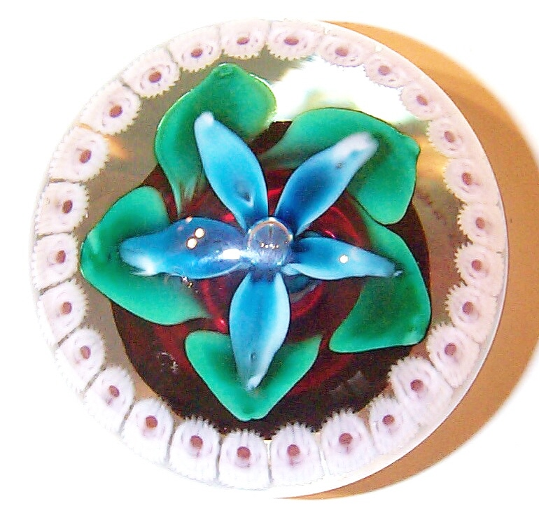 """DCP04469PE-Blue Flower Concentric....Strathearn Experimental five petal blue flower on a ruby cushion & a concentric outer ring of millefiori on a clear ground 3.15"""" x 2.5"""" & 21 ozs. Concave fire-polished smooth pontil mark base. No label. circa 1979 to 1980. acquired 01-17-03."""
