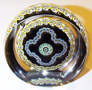 """DCP04908PPS102-1979 or 1980 Portrait Garland... Strathearn PPS102 Portrait Garland millefiori with a top and side facet on a black ground, 2.9"""" x 1.525"""" and 15.0 ozs. Flat cut polished base. Not signed, dated or numbered but circa 1979 to 1980. This one has an internal fracture through the black ground starting at the right edge of the side facet then running through the side facet cut and up to and ends about the 10 o'clock area which you can see in the photo. Obviously why it is not signed or dated but still an excellent example of this hard to find weight. acquired 01-05-10."""