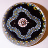 "DCP04975SP102-S80 Garland Millefiori... Strathearn SP102 limited edition Garland Millefiori on a black ground, 2.85"" x 2.35"" and 16.5 ozs. Flat cut and polished base. No label. Signed and dated 'S80' cane on base. acquired 02-18-11."
