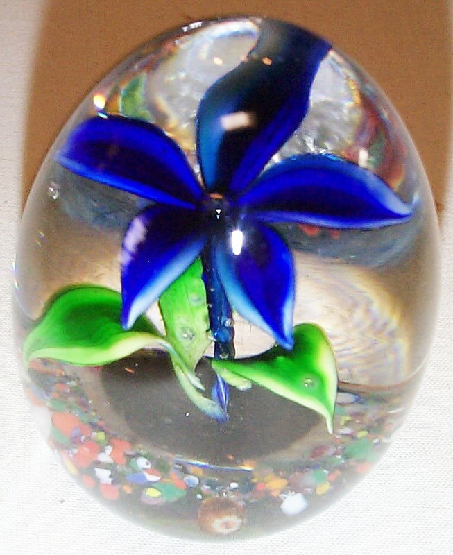 "DCP1965/66-4675P6-S-Flwr Gentian-0...Strathearn P6 ""S"" Upright Flower in Gentian blue on a Vasart & Strathearn broken cane piece ground, 3.25"" x 2.425"" and 17 ozs. Flat cut polished base. No label. Signed ""S"" cane on ground and NO date cane. The ""S"" cane appears to be placed in backwards and looks like a ""Z"" but when looked at through the base it shows the ""S"" clearly. Circa 1965 to 1966. Most likely one of the first of these flower weights made in the early years using this type ""S"" cane. acquired 10-14-05."
