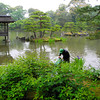 Gardening in the temple pond.<br /> These guys had the closest view of the temple than anyone else. Although it was raining, but it wasn't cold, yet they were wearing winter rain gear! I'm sure they we getting just as wet from sweat than what they would have from the rain had they not been so covered up. However the pond might filled with bad microbes that the long wet weather gear protects them from, but then they weren't wearing any gloves! I'm also not sure about the purpose of the hard hats.