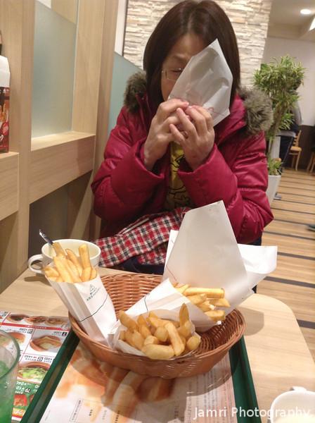 Ritsuko trying out a burger from the new Nagaokakyo MOS Burger store.