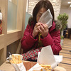 Ritsuko trying out a burger from the new Nagaokakyo MOS Burger store.
