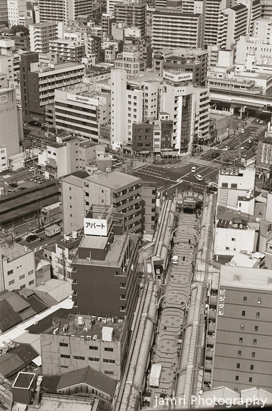 A View of the Paved Street Below.<br /> This street is the main route from the Ebisucho Subway Station to the Tsutenkaku Tower.<br /> Note Film Shot: Nikon F80 + 50f/1.8 + Y2 Yellow Filter + Circular Polariser, Kodak 400 TMax Film.<br /> Split toned with the Gimp.