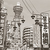Retro Osaka.<br /> This street to the south of the Tsutenkaku Tower is the only street around the tower that is still thriving with businesses. It's a place where you can get an idea of what Osaka might have been like in the 1950s. Most of the other streets seem rather quiet and are pretty much left to rot.<br /> Note Film Shot: Nikon F80 + 50f/1.8 + Y2 Yellow Filter, Kodak 400 TMax Film.<br /> Split toned with the Gimp.