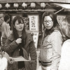In the Middle of Negotiations.<br /> Some tourist talking to a female rickshaw driver (left) who's telling them about the various tours on offer. On the streets of Shinsekai, Osaka.<br /> Note Film Shot: Nikon F80 + 50f/1.8 + PO-1 Green Filter, Kodak 400 TMax Film.<br /> Split toned with the Gimp.