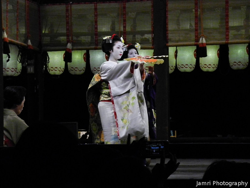 Pointing the Fans Out.<br /> Maiko (apprentice Geisha) dancing at Yasaka-jinja. During the 2013 Higashiyama Hanatouro. It's rare to catch even a glimpse of a real Maiko-san (Yes, there are plenty of tourist who pay to get dressed up as a Maiko and get their photos taken at spots around Kyoto) let alone see one perform (unless you've got the right connections), however during Hanatouro they put on some public performances.