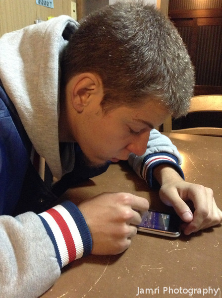 One iOS addict capturing another.<br /> Jayden on his iPhone by me with my iPod Touch.