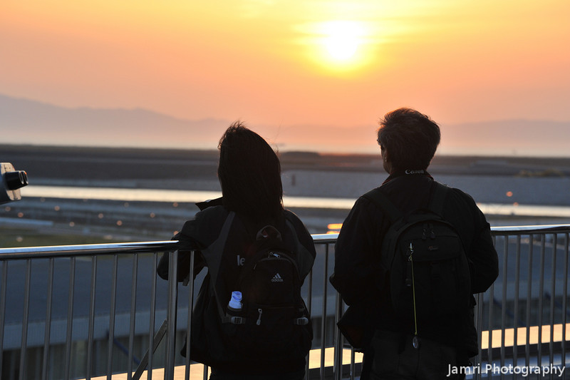 Watching the Sunset.<br /> A couple who both seem to be keen photographers (the lady had a Nikon D40 and the man a Canon 7D) pause to watch the sunset at Kansai Airport.
