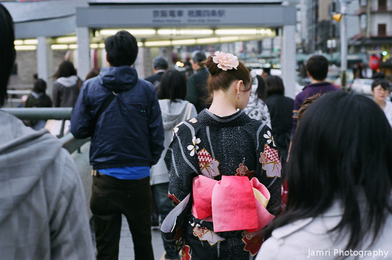 "The Lady in the Kimono.<br /> She ducks and weaves her way through the crowds with her ""younger sister"" in tow. She's not wearing the traditional make up, but some thing about her grace makes me think she's a Geiko (fully fledged Geisha).<br /> Nikon F80 + Nikkor AF 50 f/1.8 + Fujicolor PRO400"