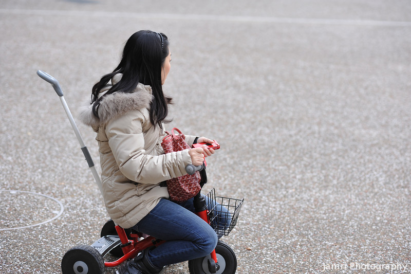 Lady on a Tricycle.<br /> This lady was sitting on the tricycle as her child was playing outside the Kyoto City Hall.