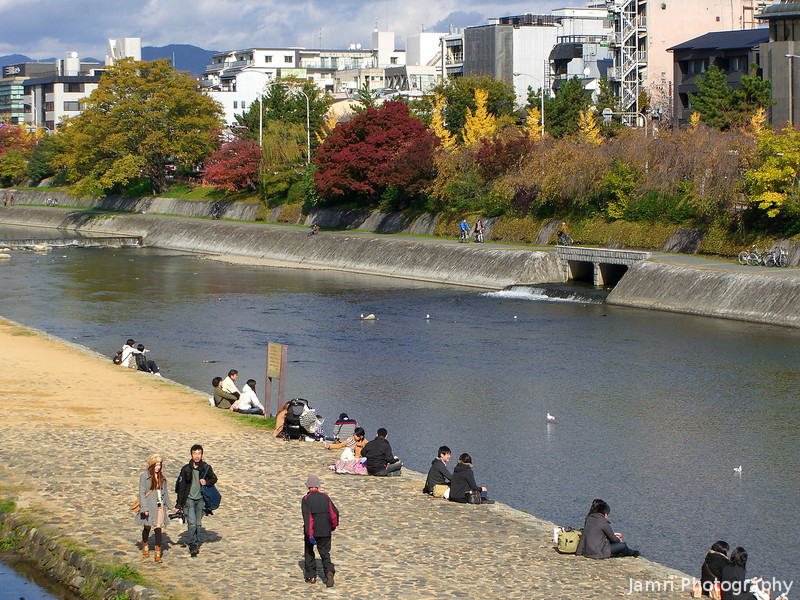 Along the Kamogawa (Kamo River).<br /> A few people out enjoying the nice autumn weather and scenery.