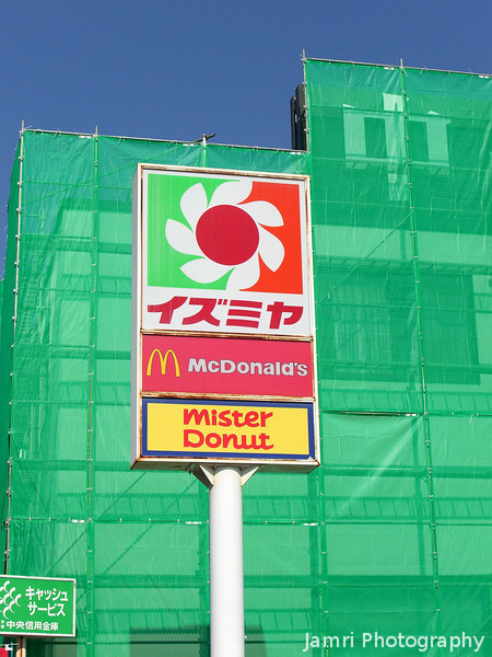 Renovations.<br /> When stopping at the local Izumiya on the way to the station, I notice that the bank next to it was under going renovations, and liked the look of the Izumiya sign against the green of the netting and the blue sky behind.
