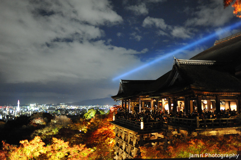 The Main Building with the City in the Background.<br /> Kiyomizu Temple, Kyoto.<br /> Note: When taking photos from here it was absolutely crowded up here and tripods weren't allowed. I just set my camera to iso6400 and continuous high speed shooting, and the lens open wide to f/2, in the hope of jagging a few good shots in the conditions. If had a D3S and 35f/1.4 I would have gone for iso12800 and f/1.4, but I was using a D700 and a 35f/2. I think 35mm is about the best focal length from this spot having been here on a number of occasions, however this was the first time under extremely crowded and low light conditions.