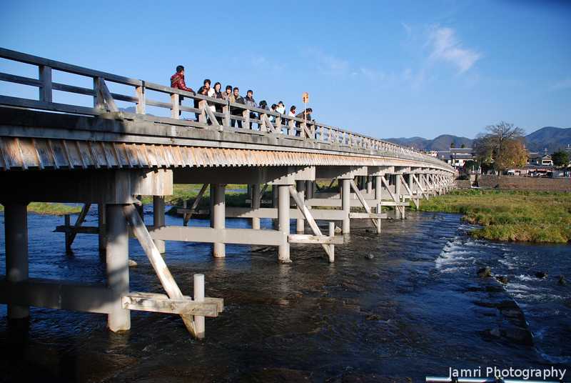 Gathering for the shot.<br /> A group of tourists gather on the big bridge at Arashiyama, Kyoto for a photograph.