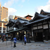 "Closer to the famous bathhouse.<br /> The bathhouse in ""Spirit Away"" (Japanese: Sen to Chihiro no kamikakushi) was based on this bathhouse's design. This bathhouse also features in the book ""Botchan"".<br /> Note: the building catching the golden light in the top left with a letter ""P"" on it, is the hotel where we stayed the night.<br /> The people wearing blue are working for the onsen, they looked really cold in their relatively thin clothing."