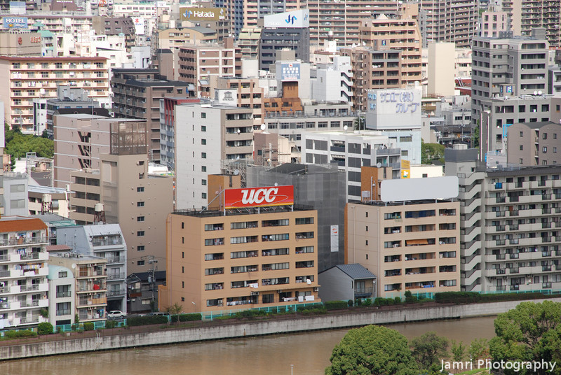 Zooming in on the building with the UCC ad.<br /> UCC is a Japanese Coffee brand, I love Coffee!<br /> From the top floor of Osaka Castle.