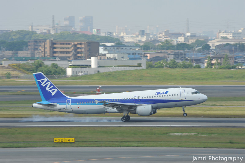 An ANA Airbus A320 touching down at Itami Airport.