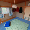 """The Master Bedroom<br /> This is our master bedroom in winter daytime configuration. At night the futon mats go on top of that green mat (which is actually a heated mat, know in Japan as """"Hot Carpet""""). In the summer months the mat and the blue carpet is replaced with a tatami covering. Under the blue carpet are tatami mats, this is a six mat room. Our house has 3 six mat bedrooms, one we use as our lounge, one is the study/guest room, and this one is our bedroom."""