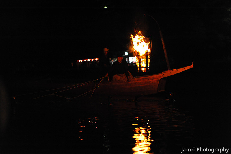 Fishing by firelight.<br /> Using trained cormorants to catch the fish.