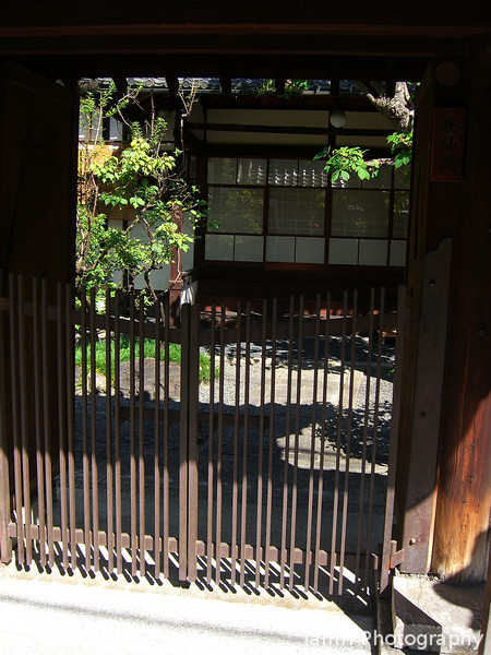 Temple Entrance.<br /> An entrance to a little temple surrounded by office blocks, shops and other buildings of commerce in the middle of Kyoto city.