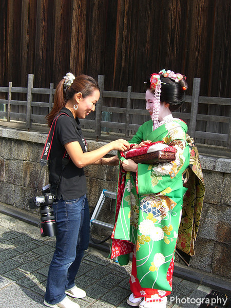 Fake Meiko.<br /> If you see someone dressed as a Meiko (Apprentice Geisha) with a personal photographer, stopping also to pose for tourists and struggling to walk in the shoes. She's probably just a tourist who's paid to be dressed up as a Meiko and get her photos taken around Kyoto.