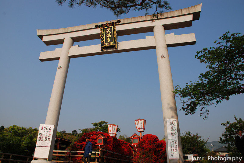 Through the gate.<br /> This gate is know as Torii this one marks the outer courts of Nagaoka Tenmangu Shrine, there are more Torii to pass through as you approach the inner Shrine. This one is the biggest of the Torii at Nagaoka Tenmangu Shrine.