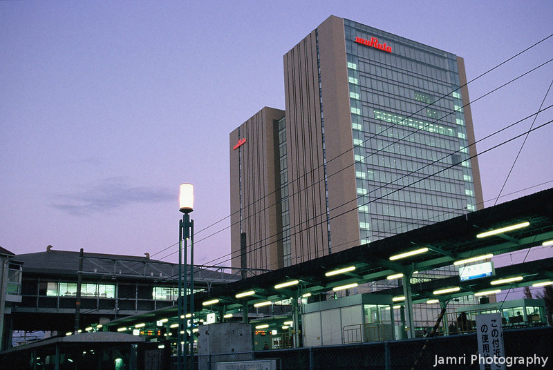 """The Murata Tower and Train Station The Murata Tower is the largest office building in Nagaokakyo. It's also the biggest business to come out of Nagaokakyo. Although you may not of heard of them, you are probably using products containing parts made by Murata. They are the one of the worlds biggest manufacturers of resistors, capacitors and other electronic components. In fact their research in making smaller components is one of the reasons mobile phones are so small today. <A href=""""http://www.murata.com"""">Visit their website for more information.</A> (Note: Film Shot, Nikon F80 + Nikkor AF 35f/2D + Fujichrome Provia 400X film)"""