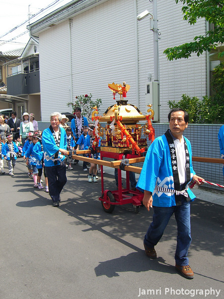 "Children's Day Parade.<br /> Snapped this shot of people bringing a Mikoshi (which is a vehicle carrying a Shinto God) past my house on Children's Day. This kind of thing to me seems like carrying the ""Ark of the Covenant"", which adds to the Japanese lost tribe theories. While I was watching the procession, one guy in the parade handed me a ""Showbag"" filled with snacks which I latter shared with some of our primary school aged students."