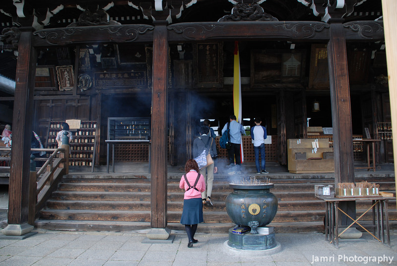 Worshippers at Mimuroto-ji.<br /> First the worshippers offer incense at the bottom of the steps before ringing the gong, by pulling a rope, to summon the temple God, then offering a prayer.