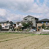 Prime Real Estate.<br /> While people (mostly non Japanese who think they know better than Japanese) bemoan the loss of traditional houses in Japan. Here is an example of tradition holding out. Here's a large field in only 2 minutes walk from the shopping centre and 5 minutes walk from the train station. I'm glad this owner is still holding on to it and hasn't had it turned into houses/apartments or another car park!<br /> Note Film Shot: Nikon F80 + Nikkor AF 35 f/2 + Fujicolor PRO400