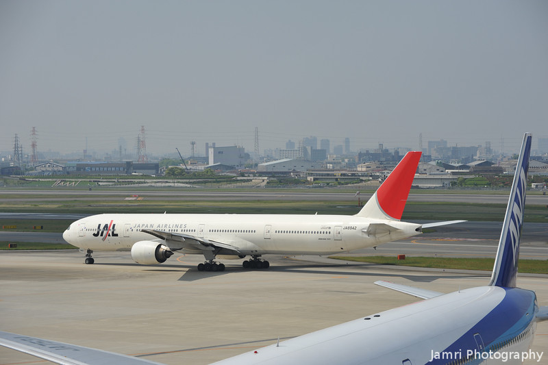 A JAL 777-300 framed by an ANA 777-300.<br /> At Itami Airport.