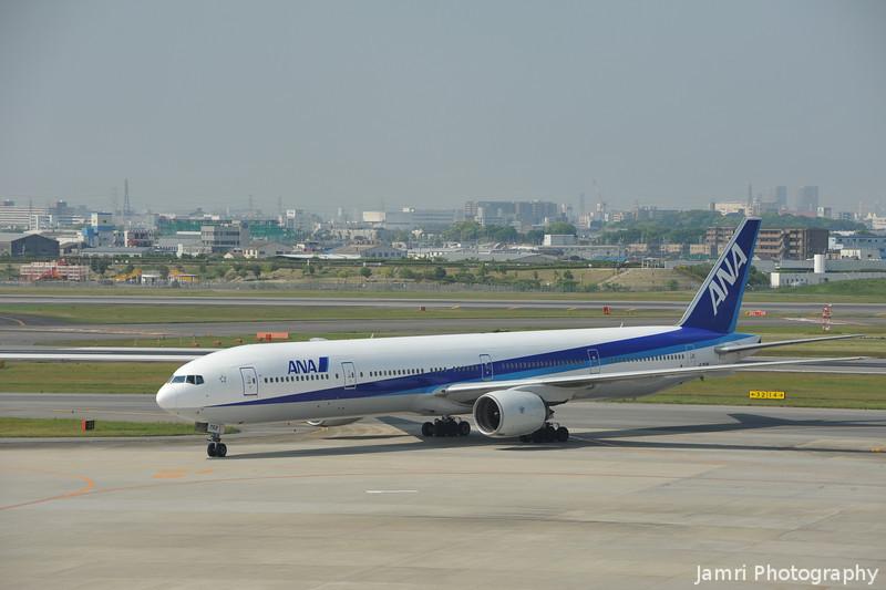 An ANA 777-300 turning towards the gates.
