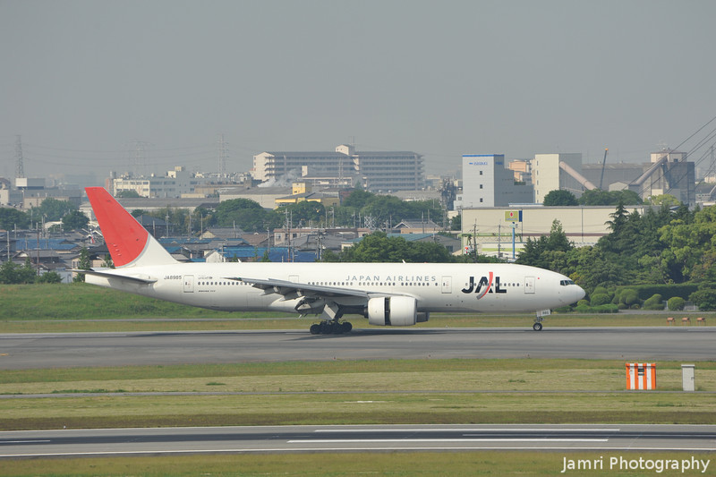 A JAL 777-200 lands at Itami Airport.<br /> Engines in Reverse Thrust.