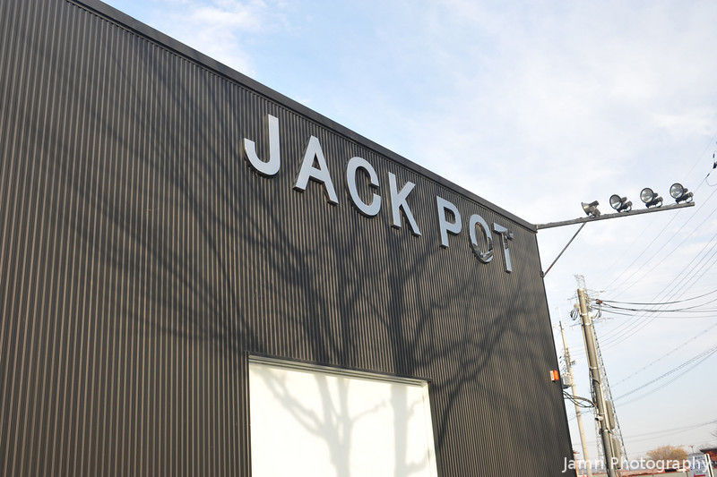 Hitting the Jack Pot!<br /> I think is a mechanic shop of some sort, but it's more likely a name someone would give to a pachinko pallor.
